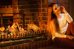 Happy woman relaxing at fireplace. Winter home. Royalty Free Stock Image