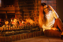 Happy woman relaxing at fireplace. Winter home. Royalty Free Stock Photo