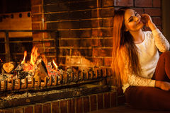 Happy woman relaxing at fireplace. Winter home. Royalty Free Stock Photos