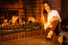 Happy woman relaxing at fireplace. Winter home. Stock Photo