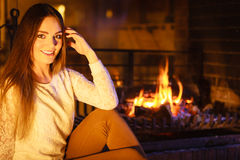 Happy woman relaxing at fireplace. Winter home. Stock Photos
