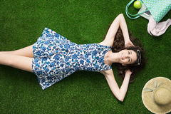 Happy woman relaxing on the grass. Happy young woman relaxing on the grass and lying down with hands behind head, relaxation and nature concept Stock Photo