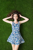 Happy woman relaxing on the grass. Happy young woman relaxing on the grass and lying down with hands behind head, relaxation and nature concept Stock Images