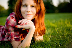 Happy woman relaxing on green grass. Royalty Free Stock Images