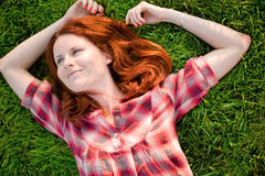 Happy woman relaxing on green grass. Royalty Free Stock Photos