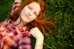 Happy woman relaxing on green grass. Stock Photos