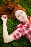Happy woman relaxing on green grass. Stock Image