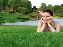 Happy woman relaxing on green grass in the garden. Stock Photo