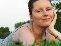 Happy woman relaxing on green grass in the garden. Royalty Free Stock Photos