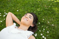 Happy woman relaxing with hand behind head on grassland Stock Photo