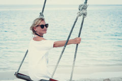 Happy woman relaxing with hanging swing on tropical beach Royalty Free Stock Photography