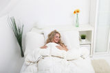 Happy woman relaxing on her back in bed Royalty Free Stock Images
