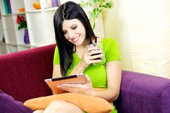 Happy woman relaxing at home with coffee and tablet Royalty Free Stock Photos