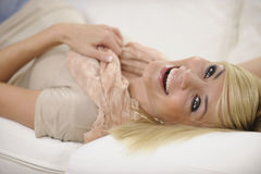 Happy woman relaxing at home laughing. On sofa Royalty Free Stock Photography