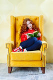 Happy woman relaxing at home and reading a book Stock Photos