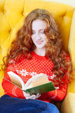 Happy woman relaxing at home and reading a book Royalty Free Stock Image