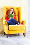 Happy woman relaxing at home and reading a book Royalty Free Stock Photos