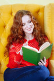 Happy woman relaxing at home and reading a book Stock Photography