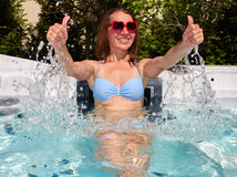 Happy woman relaxing in hot tub. Young beautiful woman relaxing in a hot tub royalty free stock images