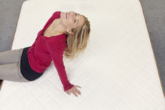 Happy woman relaxing on mattress with head back in furniture store Royalty Free Stock Photos