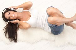 Happy woman relaxing with music. Happy young woman lying on floor, listening to music through headphones, smiling, pulling legs up Royalty Free Stock Image