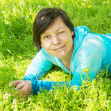 Happy woman relaxing in the park , lying in green grass and spri Royalty Free Stock Photo