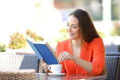 Happy woman reading a book stirring the coffee in a bar stock images