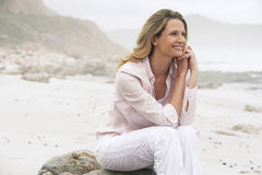 Happy Woman Relaxing On Rock At Beach Royalty Free Stock Images