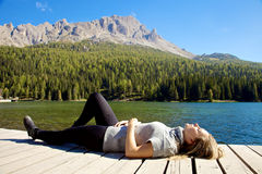 Happy woman relaxing in summer in front of lake and mountains in Europe Stock Photography