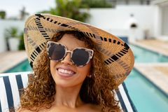 Happy woman relaxing on a sun lounger near swimming pool at the backyard of home. Front view of happy mixed-race woman relaxing on a sun lounger near swimming royalty free stock photos