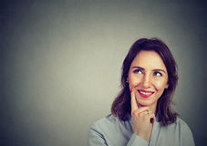 Happy woman remembering looking up at side smiling royalty free stock images