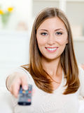 Happy woman with remote control sitting Stock Image