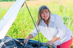 Happy woman repairing the car Stock Photography