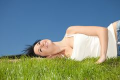 Happy woman rest on the green grass Royalty Free Stock Image