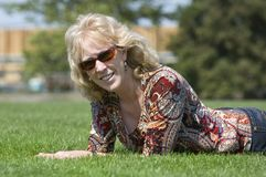 Happy woman resting. Happy professional blond woman in sunglasses laying on the grass during a lunch break Royalty Free Stock Images