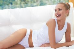Happy Woman Resting on Couch Wearing Underwear Stock Images