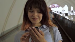 Happy woman rides escalator down to subway using a smartphone. Pretty caucasian young brunette woman. Stands on an escalator that goes down to bottom of stock footage
