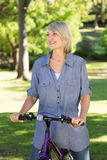Happy woman riding bicycle Stock Images