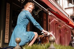 Happy woman riding a bicycle on street of the city. Happy charming young woman riding a bicycle on the street of the city Royalty Free Stock Images