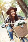 Happy woman riding bike bicycle in fall autumn park Royalty Free Stock Image