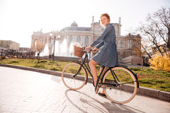 Happy woman riding a bike near the theatre stock images