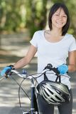 Happy woman riding bike in sunny park royalty free stock photos