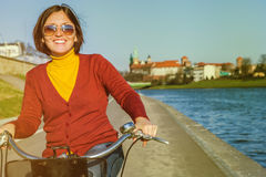 Happy woman riding by bysicle along the waterfront Royalty Free Stock Image