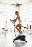 Happy woman riding exercise bike in gym Royalty Free Stock Photography