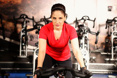 Happy woman riding an exercise bike in gym Royalty Free Stock Image