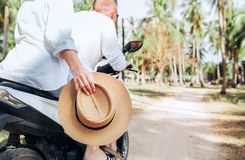 Happy woman riding motorbike with her boyfriend during their tropical vacation under palm trees Straw hat close up image royalty free stock photo