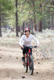 Happy woman riding mountain bike on wilderness trail Stock Images