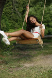 Happy woman riding on a swing in the park Stock Photography