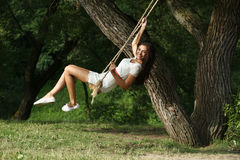 Happy woman riding on a swing in the park royalty free stock images