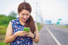 Happy woman at roadside is playing her mobile phone to communica Royalty Free Stock Image